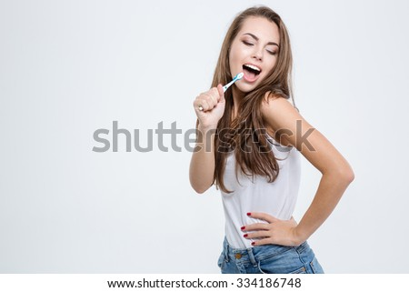 Portrait of a happy woman cleaning her teeth with toothbrush isolated on a white background - stock photo