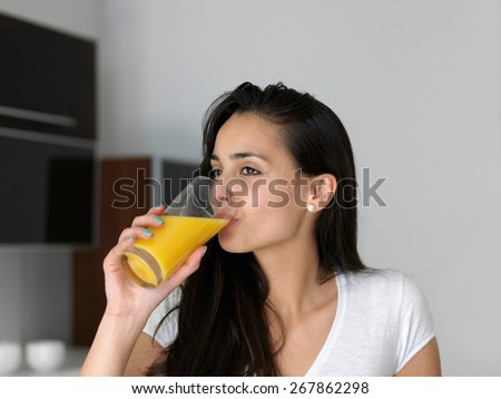 Portrait of a happy woman drinking juice in her kitchen - stock photo
