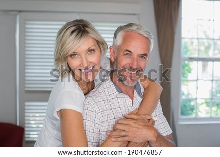 Portrait of a happy woman embracing mature man from behind at home