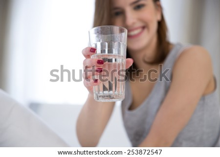 Portrait of a happy woman holding glass of water. Focus on glass