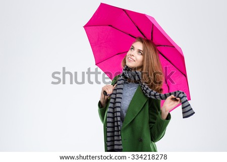 Portrait of a happy woman holding pink umbrella isolated on a white background and looking up - stock photo