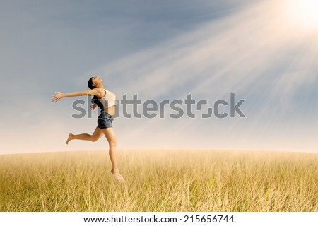 Portrait of a happy woman jumping in wheat field