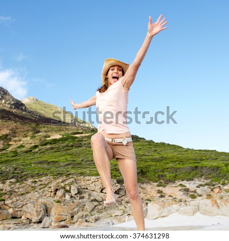 Portrait of a happy woman jumping outdoors - stock photo