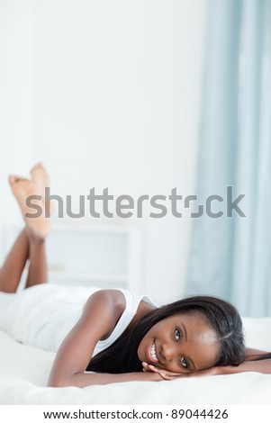 Portrait of a happy woman lying on her belly in her bedroom - stock photo