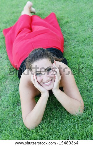 Portrait of a happy woman lying on the grass.