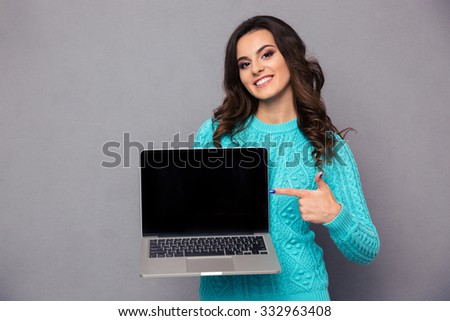 Portrait of a happy woman pointing finger on blank laptop computer screen over gray background and looking at camera - stock photo