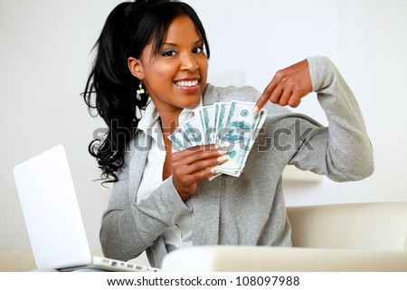 Portrait of a happy woman pointing plenty of cash money - stock photo