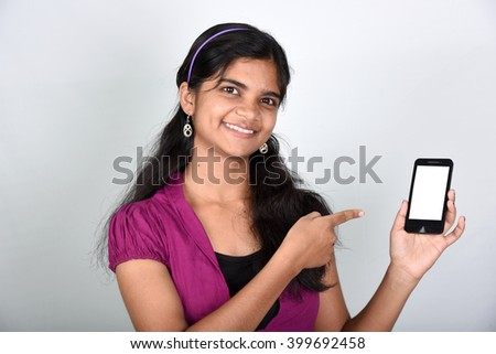 Portrait of a happy woman showing blank smartphone screen over gray background