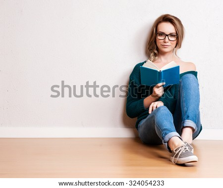 Portrait of a happy woman sitting on the floor with book on gray background and looking at camera