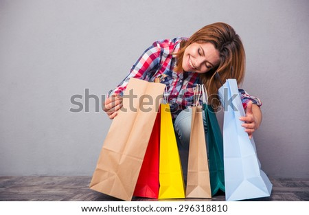 Portrait of a happy woman sitting with shopping bags in studio. Looking at camera - stock photo