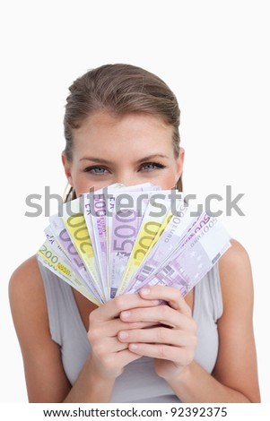 Portrait of a happy woman smelling bank notes against a white background - stock photo