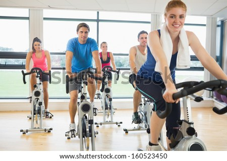 Portrait of a happy woman teaches exercise bike class to four people at gym - stock photo