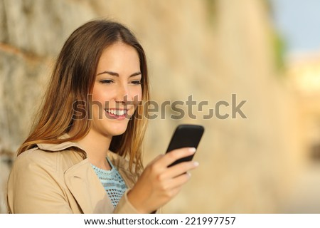 Portrait of a happy woman using a smart phone in an old town with an unfocused background