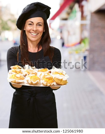Portrait Of A Happy Woman While Holding Cupcake, Outdoor - stock photo
