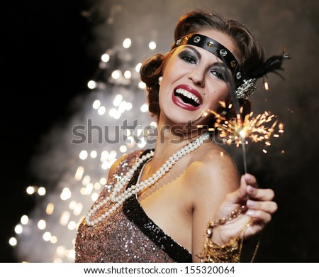 Portrait of a happy woman who is holding bengal lights over a sparkling background