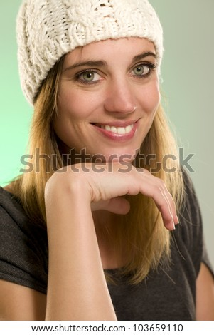 portrait of a happy woman with a winter cap in front of green background - stock photo