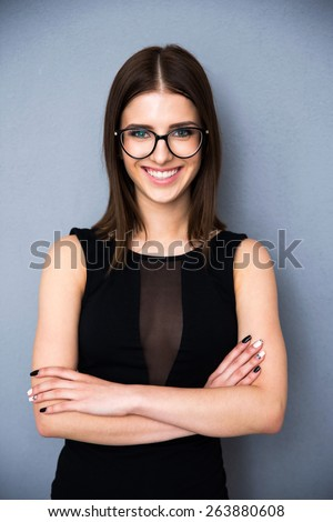Portrait of a happy woman with arms folded and glasses standing over gray background. Wearing in fashion black dress. Looking at camera - stock photo