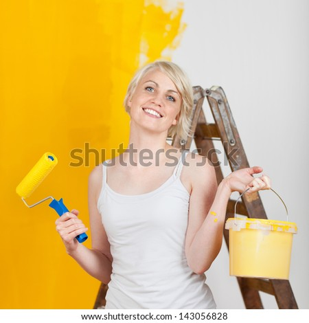 portrait of a happy woman with paint tools - stock photo