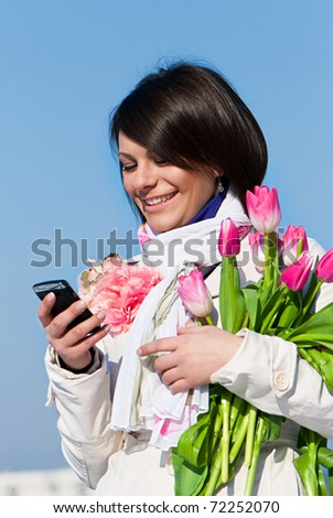 Portrait of a happy women with pink tulips typing a text message on cellphone - stock photo