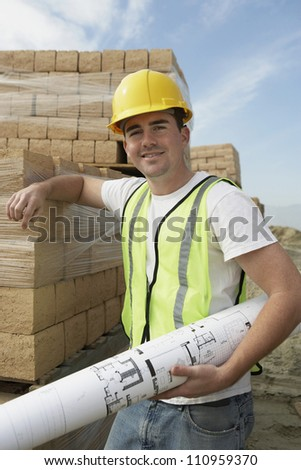 Portrait of a happy worker holding blueprint at construction site - stock photo
