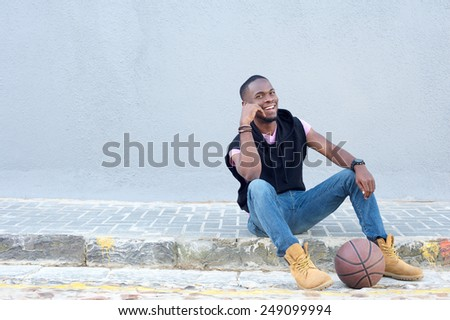 Portrait of a happy young african american man sitting with basketball  - stock photo