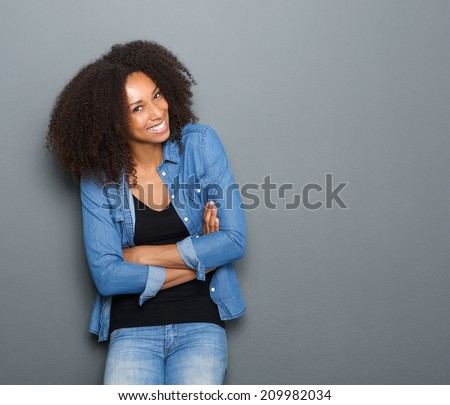 Portrait of a happy young african american woman posing with arms crossed - stock photo