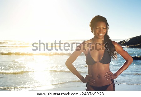 Portrait of a happy young african american woman smiling at the beach