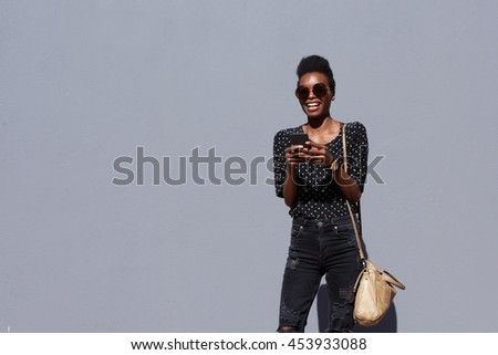 Portrait of a happy young african american woman with bag and mobile phone standing against gray background - stock photo