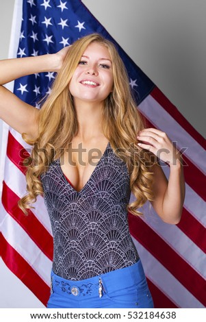 Portrait of a happy young blonde woman on a background of the American flag