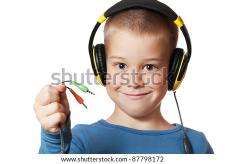 Portrait of a happy young boy listening to music on headphones against white background - stock photo