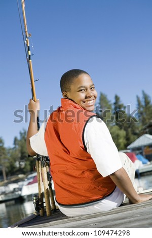 Portrait of a happy young boy looking over shoulder while sitting on pier with fishing rods - stock photo