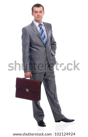 Portrait of a happy young business man holding suitcase on white background