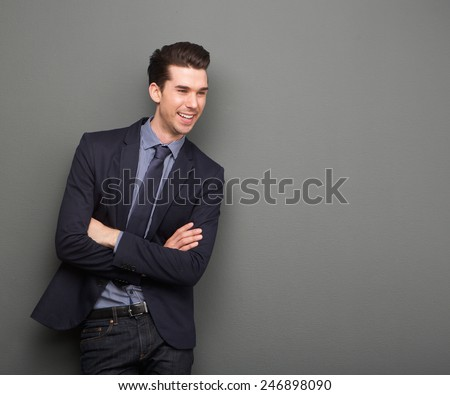 Portrait of a happy young business man standing with arms crossed on gray background - stock photo