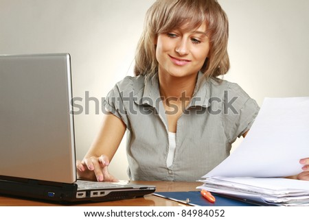Portrait of a happy young business woman at work , at her desk - stock photo