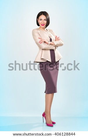 Portrait of a happy young business woman brunette isolated on blue background - stock photo