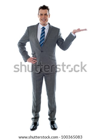 Portrait of a happy young businessman presenting a product against white background - copy space