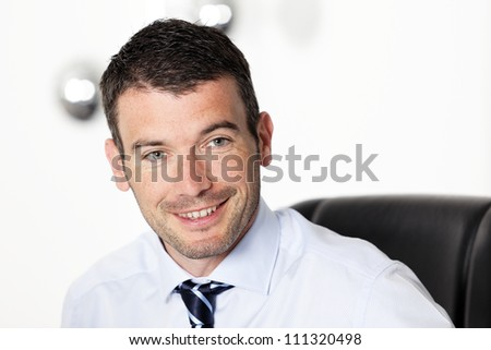 Portrait of a happy young businessman sitting at office - stock photo