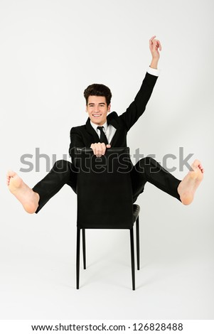 Portrait of a happy young businessman sitting in a chair with raised arm, on white background - stock photo
