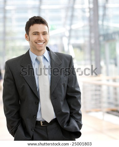 Portrait of a happy young businessman, smiling, indoor. - stock photo