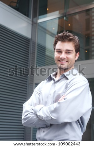 Portrait of a happy young businessman standing outside office