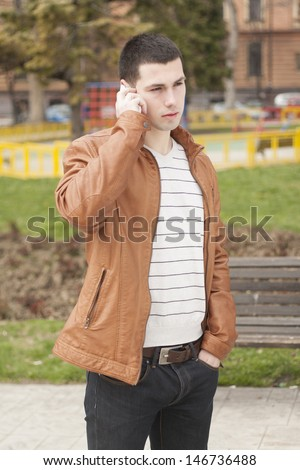 Portrait of a happy young businessman walking and talking on the phone in park - stock photo