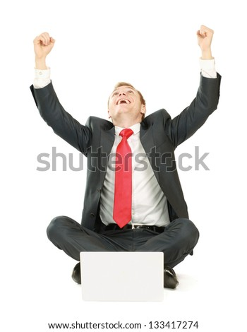 Portrait of a happy young businessman working on laptop against white background