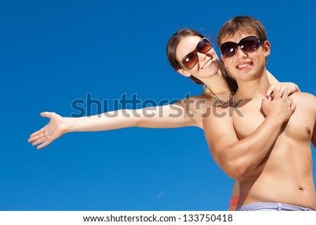 Portrait of a happy young couple enjoying at beach - stock photo