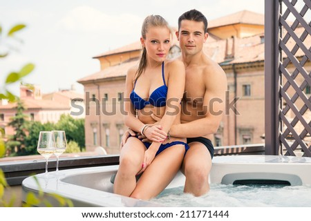 Portrait of a happy young couple enjoying Jacuzzi.  - stock photo