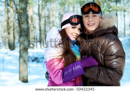 Portrait of a happy young couple having a rest in winter park.