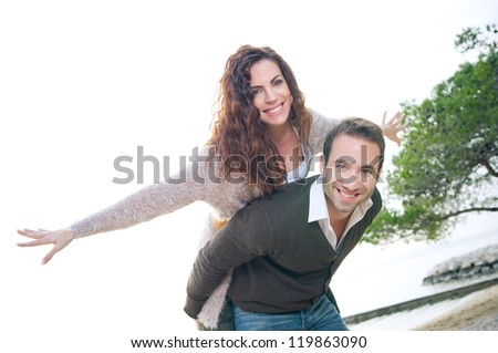 Portrait of a happy young couple having fun on the beach - stock photo