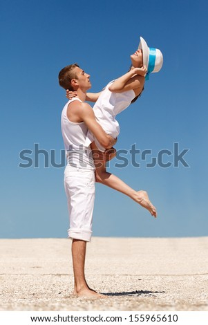 Portrait of a happy young couple having fun on the beach. Young man lifting his woman on beach.Couple enjoying a summer vacation. - stock photo