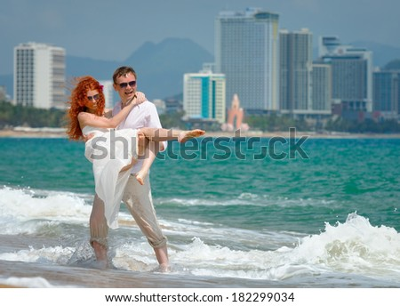 Portrait of a happy young couple having fun on the beach. Young man lifting his woman on beach. Couple enjoying a summer vacation. - stock photo