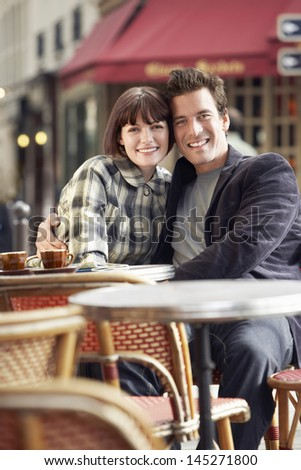 Portrait of a happy young couple sitting at an outdoor cafe - stock photo