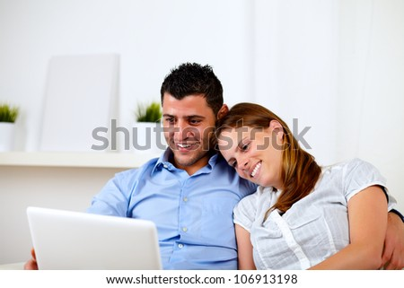 Portrait of a happy young couple sitting on sofa with a laptop at home